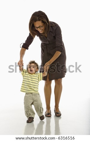 African American mid adult mother holding arms of toddler son learning to walk. - stock photo