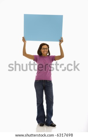 African American mid adult woman holding sign over head smiling at viewer.