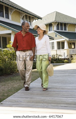 African American middle aged couple holding hands strolling on wooden walkway. - stock photo