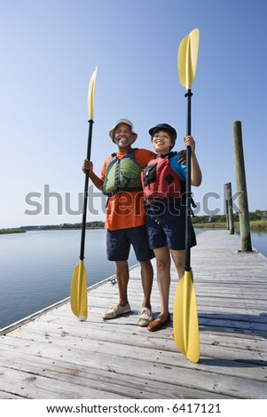 African American middle-aged couple standing on boat dock holding paddles and smiling at viewer. - stock photo