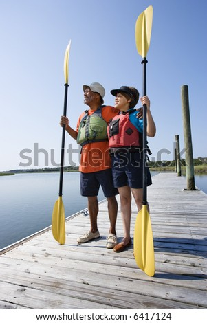 African American middle-aged couple standing on boat dock holding paddles wearing life preservers. - stock photo