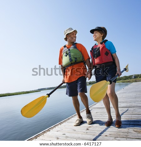 African American middle-aged couple walking on boat dock holding hands and carrying paddles. - stock photo