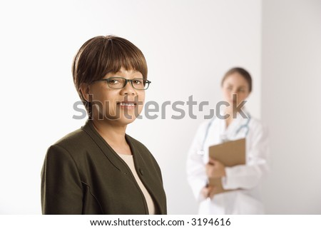 African American middle-aged female patient woman smiling looking at viewer with Caucasian mid-adult female doctor standing in background. - stock photo