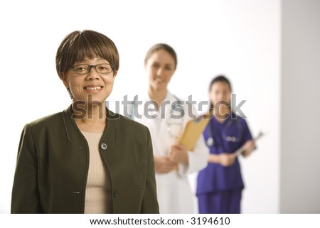 African American middle-aged woman smiling and looking at viewer with Caucasian mid-adult female doctor and Asian Chinese mid-adult female physician's assistant standing in background. - stock photo