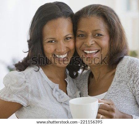 African American mother and adult daughter hugging - stock photo