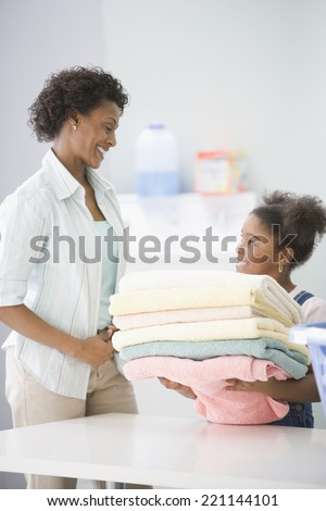 African American mother and daughter doing laundry - stock photo