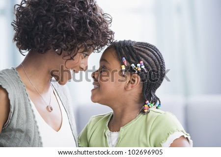 African American mother and daughter smiling at each other - stock photo