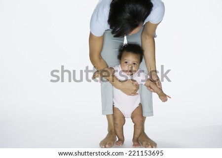 African American mother helping baby stand - stock photo
