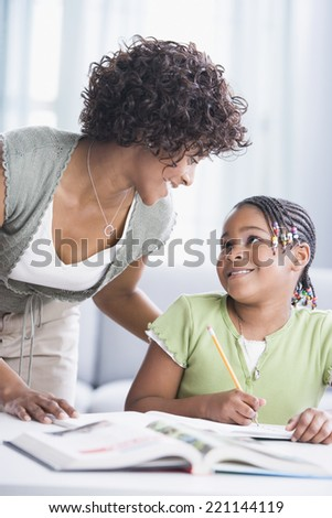African American mother helping daughter with homework - stock photo