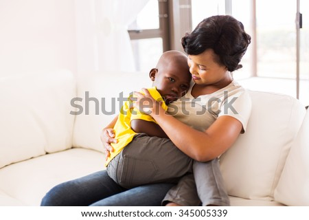 african american mother hugging her son at home - stock photo