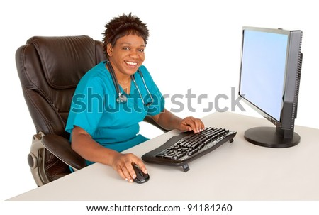 African American Nurse Smiling at Camera While Sitting at her Desk - stock photo