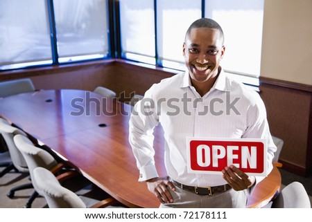 African American office worker holding open sign in empty boardroom