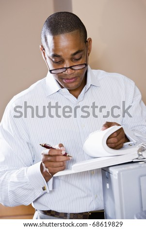 African American office worker reviewing document binder, leaning on printer - stock photo