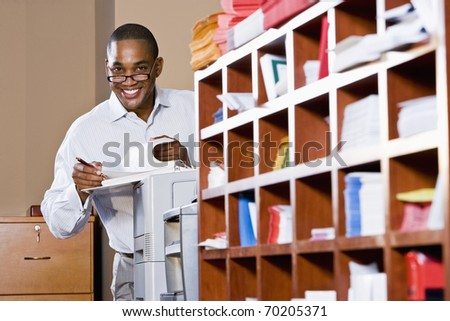 African American office worker reviewing document binder, leaning on printer in mailroom - stock photo