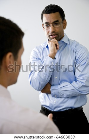 African American office worker, 40, standing and listening to colleague talking