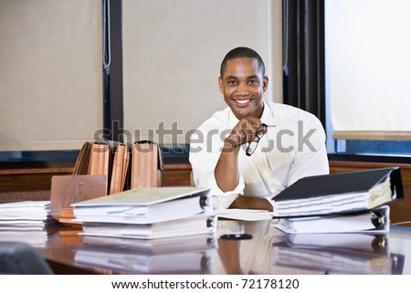 African American office worker with stacks of documents on table in boardroom