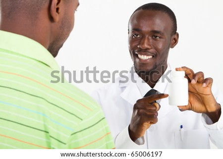 african american pharmacist explaining how to take medicine to customer - stock photo