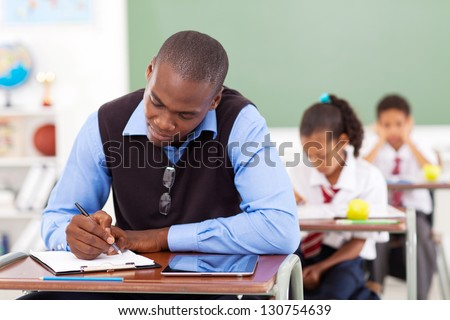 African American primary school teacher preparing a lesson in classroom - stock photo