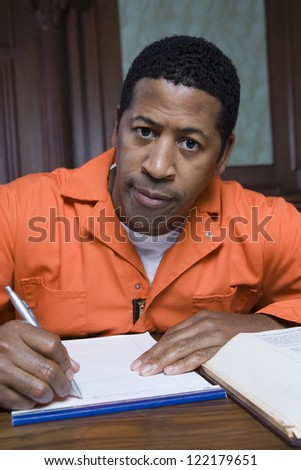 African American prisoner confessing crime on paper - stock photo