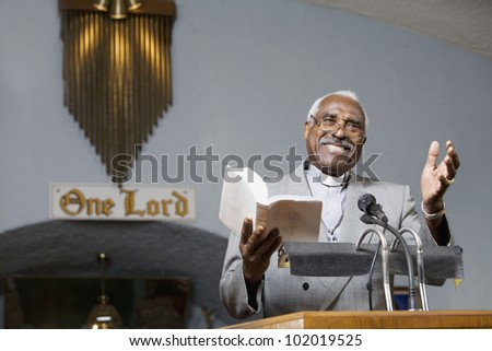 African American Reverend preaching in church - stock photo