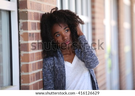 African American, sad, bad mood, depressed, adult student, girl smiling outside white teeth, university, united states, model, teenager, teenage, teen, young beautiful girl, female portrait, black,  - stock photo