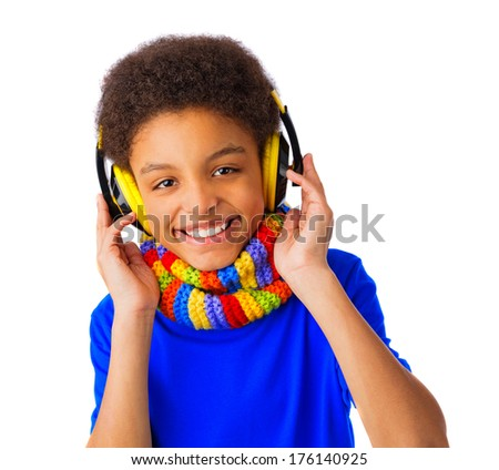 African American school boy smiling and listening to music with yellow headset and colorful scarf. Over white background, isolated, with copy space. - stock photo