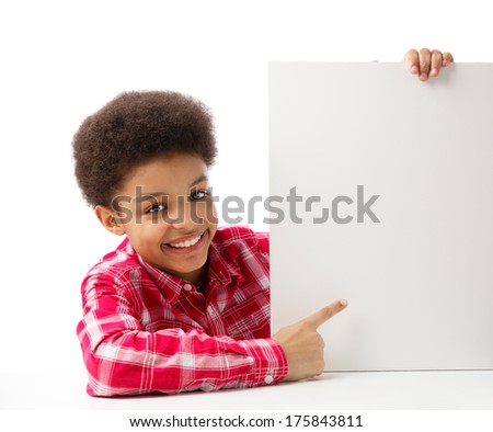 African American school boy, teenager smiling and pointing at empty white blank board, education and school concept. Isolated, over white background, with copy space. - stock photo