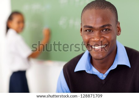 african american school teacher and student in front of chalkboard - stock photo