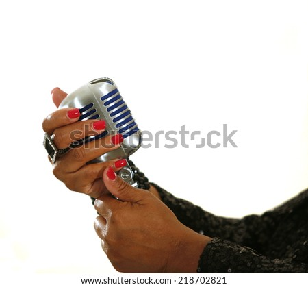 African-American singer's hands holding microphone at performance isolated on white - stock photo