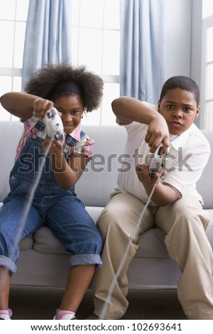 African American sister and brother playing video games - stock photo