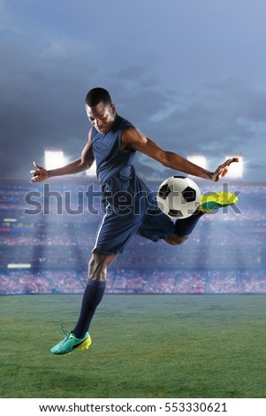 African American soccer player kicking ball with heel inside stadium