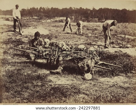 African American soldier of a burial party on battle-field of Cold Harbor seated next to a stretcher containing remains of Union soldiers who perished in the battles of Gaines' Mill and Cold Harbor. - stock photo
