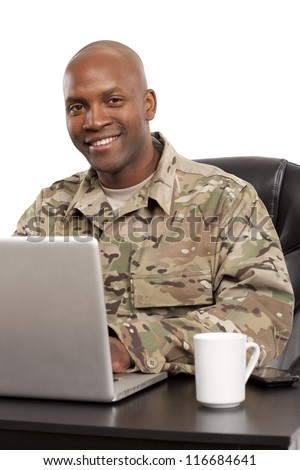 African American soldier smiles while working on a computer - stock photo