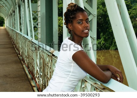 African American stands on bridge - stock photo