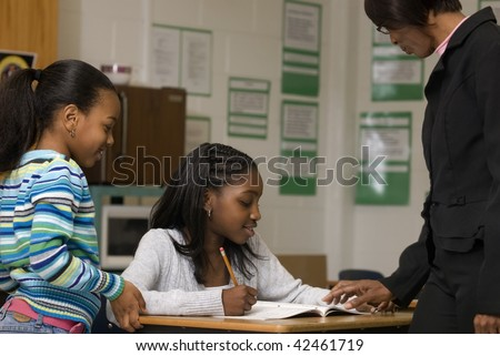 African American student gets help from teacher while another student look at the math problem
