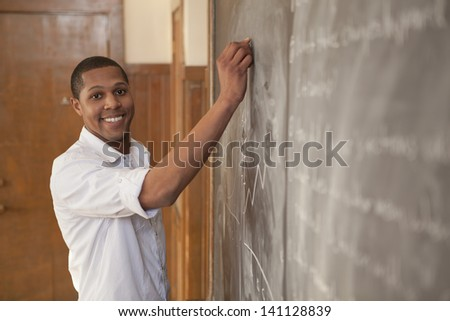 African American student happily writing on a chalkboard in classroom - stock photo