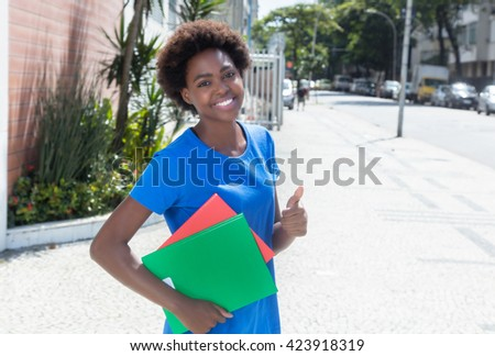 African american student in a blue shirt showing thumb up outdoor in city with streets and buildings in the background - stock photo