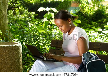 african american student studying computer in the park - stock photo