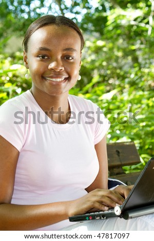 african american student studying computer outdoors - stock photo