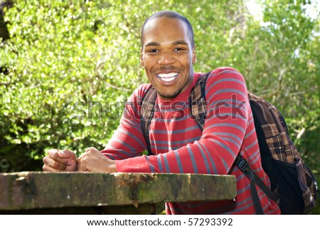 African American student wearing backpack sitting at outdoor table - stock photo