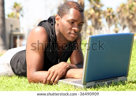 African American Student Working on a Laptop Outdoors - stock photo