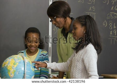 African American students and teacher search the globe - stock photo