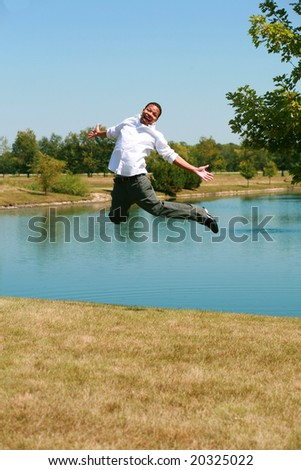 African-American teen boy by lake jumping in air - stock photo