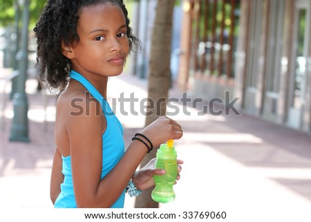 African American Teenager Girl Having Fun and Blowing Bubbles, City Street - stock photo