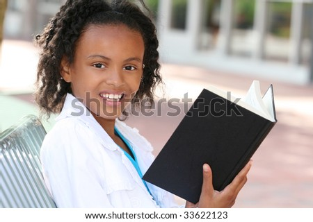 African American teenager girl reading a book on a bench outdoors, city street