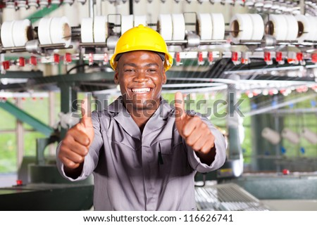african american textile worker thumbs up in front of weaving loom