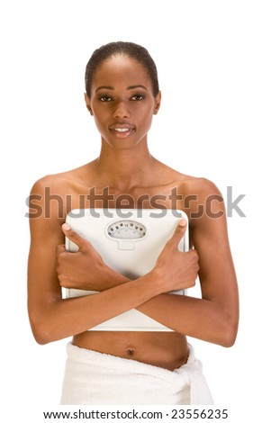 African American topless woman with her hips wrapped in bath towel covers her chest with weighscales confident in her success with weight control dieting strategy results - stock photo