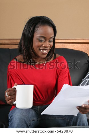 African American woman all smiles reading a letter with good news - stock photo