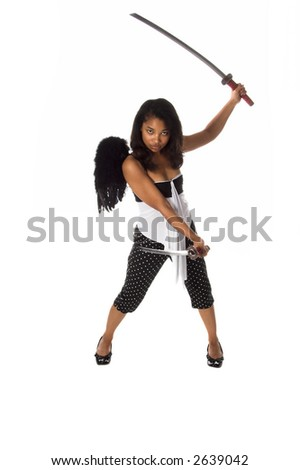 African American woman as a Ninja Angel with black feather wings and an intense expression attacks with a pair of Samurai Swords - stock photo