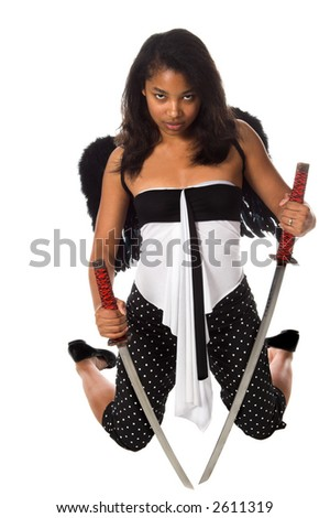 African American woman as a Ninja Angel with black feather wings and an intense expression kneels with a pair of Samurai Swords